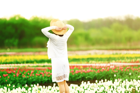 Happy woman on blooming field of tulips