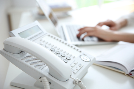 Businesswoman with office IP telephone Stock Photo