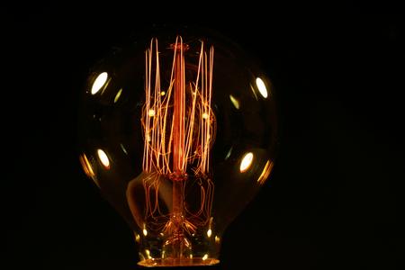 Ampoule éclairée sur fond noir Banque d'images