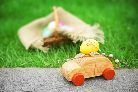 Decorative toy car with pussy willow and Easter egg on green grass background Stock Photo