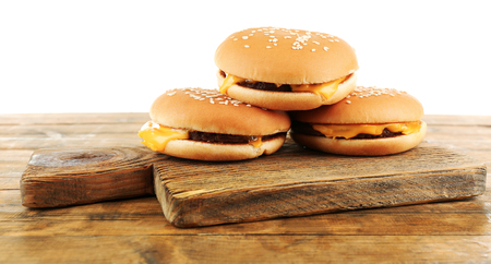 Tasty cheeseburgers on cutting board, isolated on white Banco de Imagens