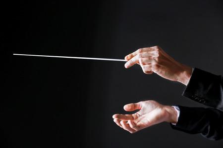 Orchestra conductor hands on dark background