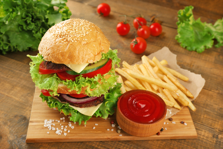 Double hamburger with fries on wooden background