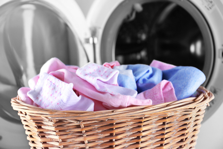 Baby clothes and washing machine, close up