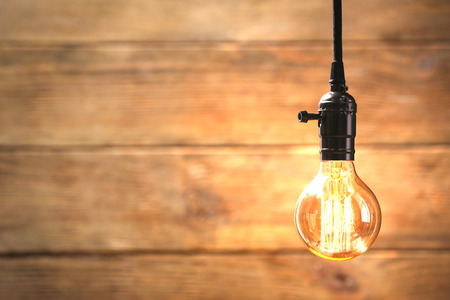 Bright bulb on wooden background 版權商用圖片