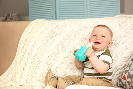 Baby drinking water on a couch Stock Photo