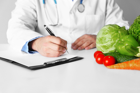 Doctor counting calories in hospital Stock Photo