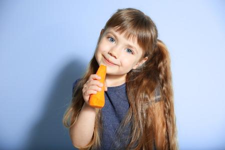 Niña con zanahoria en el fondo de la pared Foto de archivo
