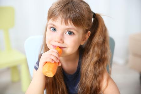 Niña con zanahoria en la sala de estar