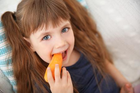 Niña con zanahoria sentada en el sofá Foto de archivo