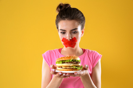 Woman with tied mouth holding hamburger on yellow background Stock fotó