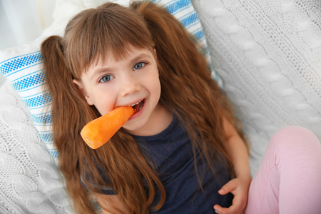 Little girl with carrot sitting on sofa