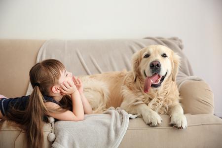 Little girl and big kind dog on sofa