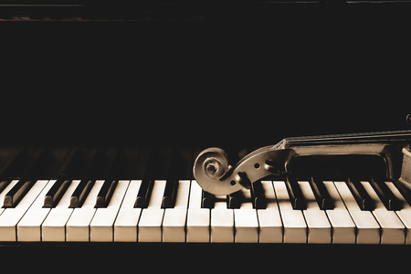 Violin neck lying on piano keys, close up Stock fotó