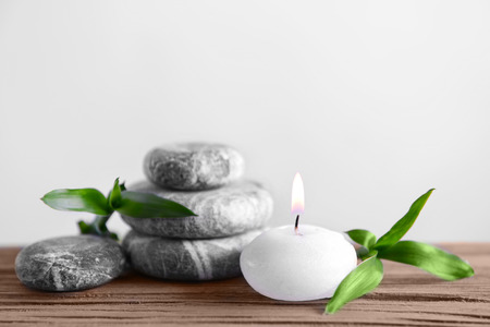 Gray spa stones with candle on light background 写真素材