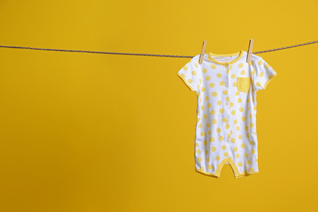 Baby clothes hanging on rope on yellow background Stok Fotoğraf
