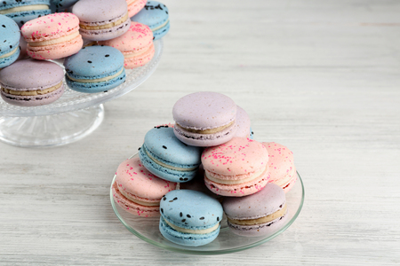 Tasty macaroons on stand and glass plate on wooden table