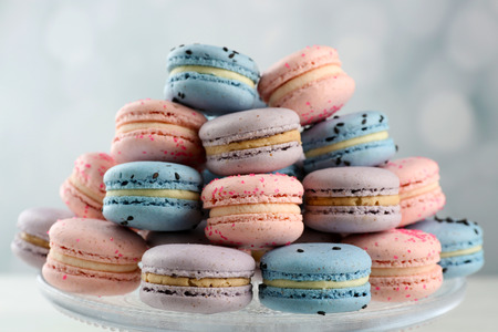 Tasty macaroons on stand on wooden table Stock Photo