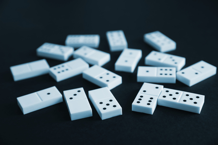 Heap of dominoes on black background