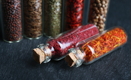 Different spices in small glass bottles on black table