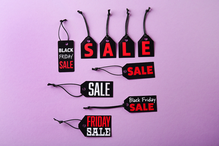Paper tags with strings and word sale on purple background