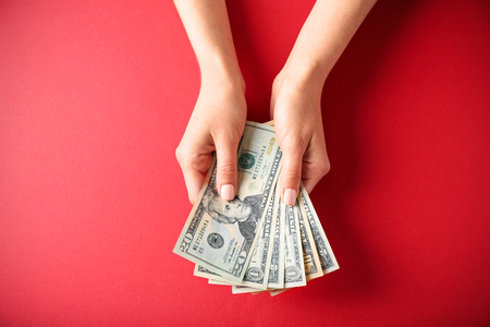 Woman hands holding money on red background