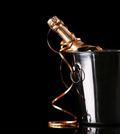Bouteille de champagne avec de la glace dans un seau sur fond noir Banque d'images