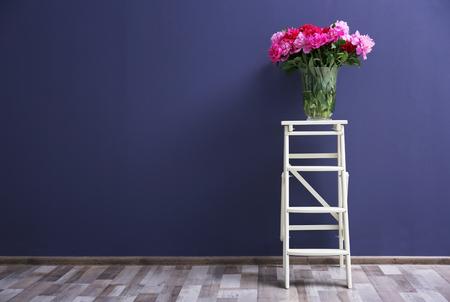 Beautiful peony bouquet on dark wall background