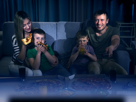 Happy lovely family watching TV with pizza