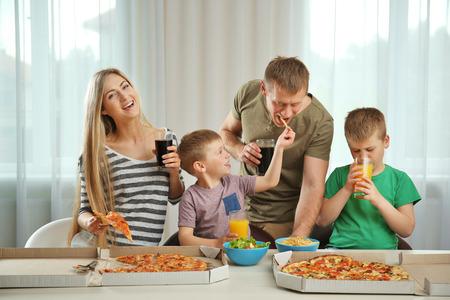 Familia encantadora feliz comiendo pizza