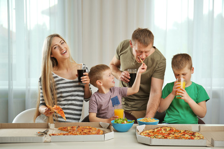 Glückliche schöne Familie, die Pizza isst Standard-Bild - 108839008