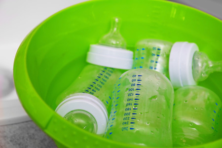 Sterilizing baby bottles in plastic green basin Stock Photo