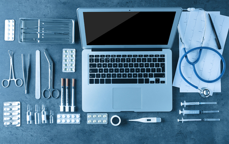 Medical tools set with laptop on dark gray background