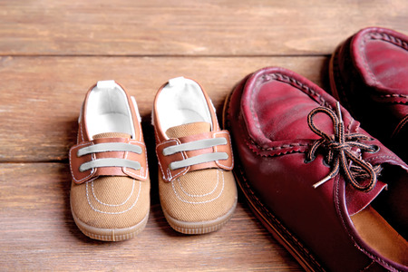 Big and small shoes on wooden background Stock Photo