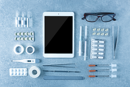 Medical tools set with tablet on gray background