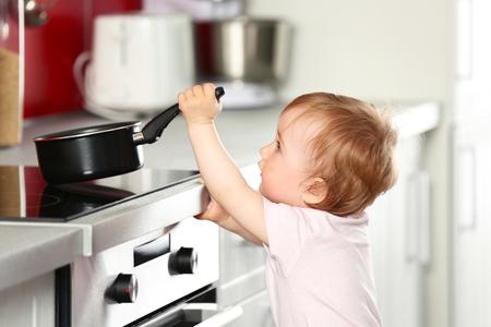 Piccolo bambino che gioca con padella e cucina elettrica in cucina