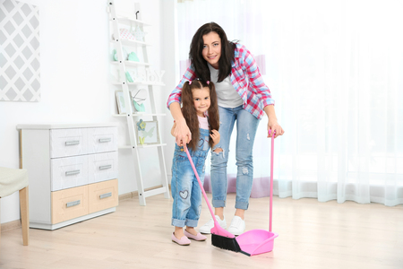 Daughter and mother sweeping together in room Stock Photo