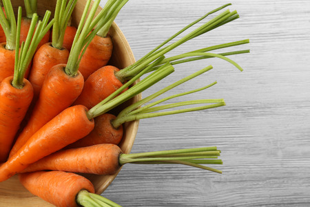 Fresh carrots in a bowl on wooden background Stock Photo