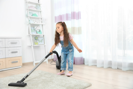 Cute little girl using vacuum cleaner in room