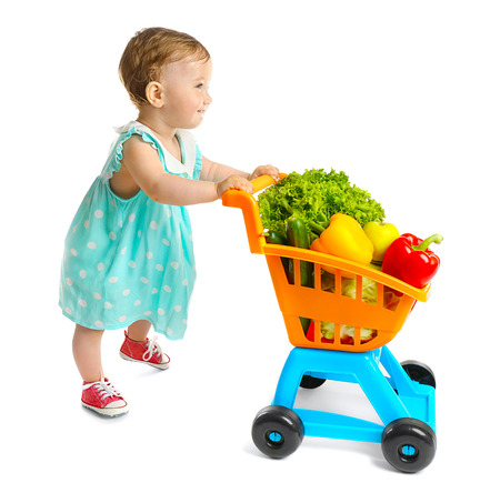 Cute baby girl with vegetables in supermarket trolley, isolated on white Foto de archivo - 107533968