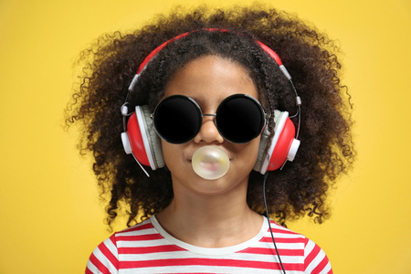 Afro-American little girl with headphones and sunglasses chewing gum on yellow background Stock Photo