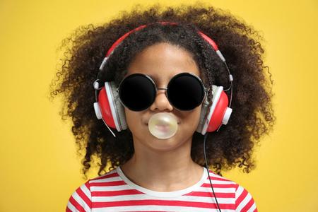Afroamerikanisches kleines Mädchen mit Kopfhörern und Sonnenbrillen, die Kaugummi auf gelbem Hintergrund kauen