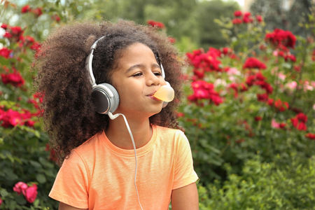 Afro-American little girl with sunglasses and headphones chewing bubblegum in park Stok Fotoğraf