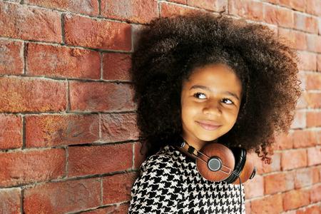 Petite fille afro-américaine avec un casque sur fond de mur de brique