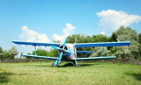 Old airplane on green grass Фото со стока