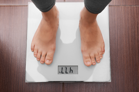 Female feet standing on a scales in bathroom