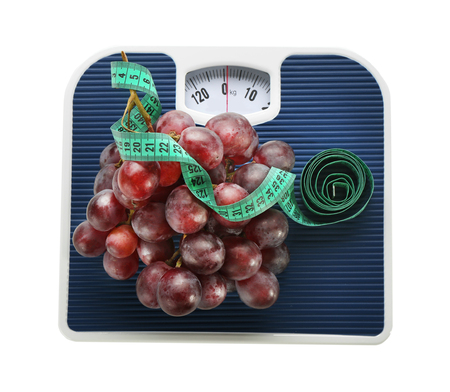 Bathroom scale with grapes and measuring tape on white background