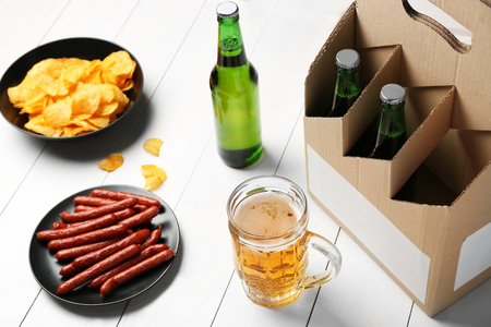 Paper beer package with mug, sausages and chips on wooden background 免版税图像