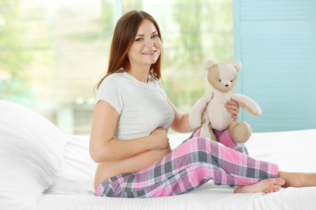 Pregnant woman sitting on a bed with teddy bear