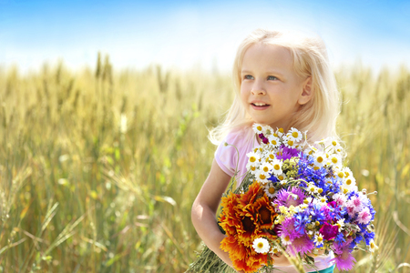 Little girl with bouquet of flowers in the field Stock Photo